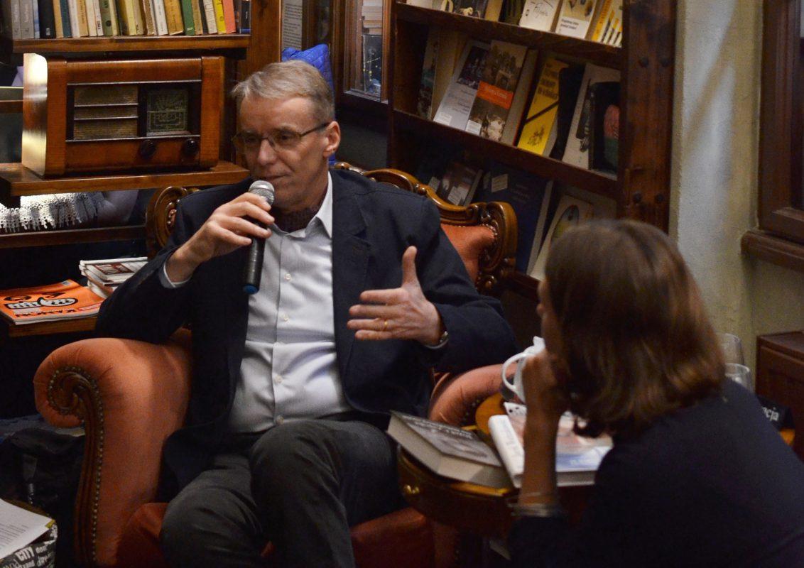 henryk Wozniakowski parle de Czapski. Il est assis sur le fond des livres. photographie couleur